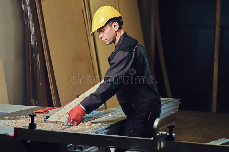 O carpinteiro está inclinando-se na tabela de madeira foto de stock royalty free