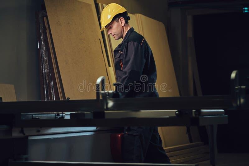 O carpinteiro está inclinando-se na tabela de madeira imagem de stock royalty free