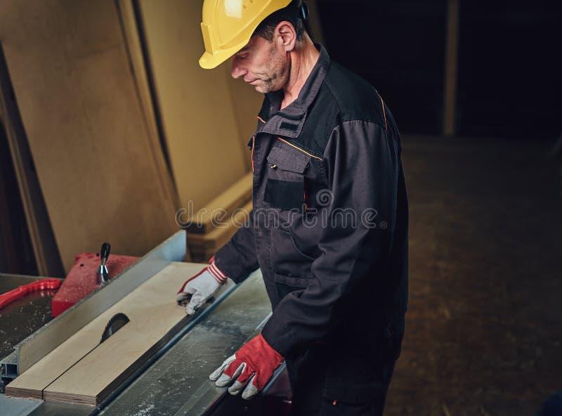 O carpinteiro está inclinando-se na tabela de madeira imagens de stock royalty free
