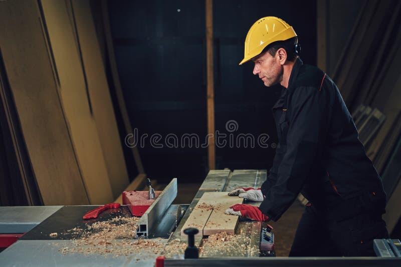 O carpinteiro está inclinando-se na tabela de madeira fotografia de stock