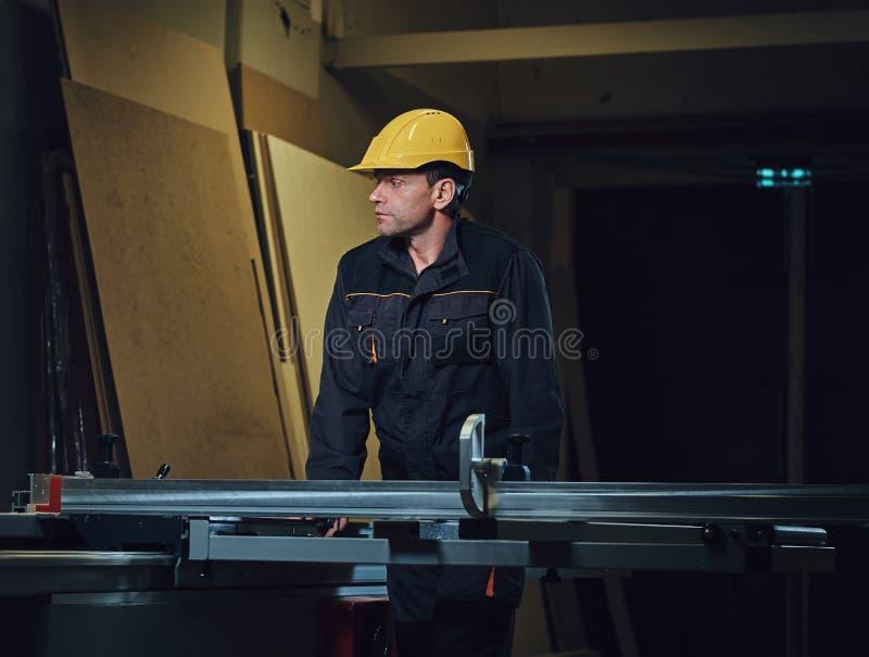 O carpinteiro está inclinando-se na tabela de madeira foto de stock