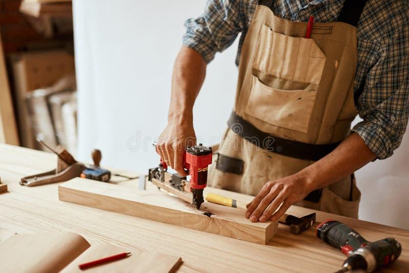 O carpinteiro fura um furo com uma broca elétrica imagens de stock royalty free