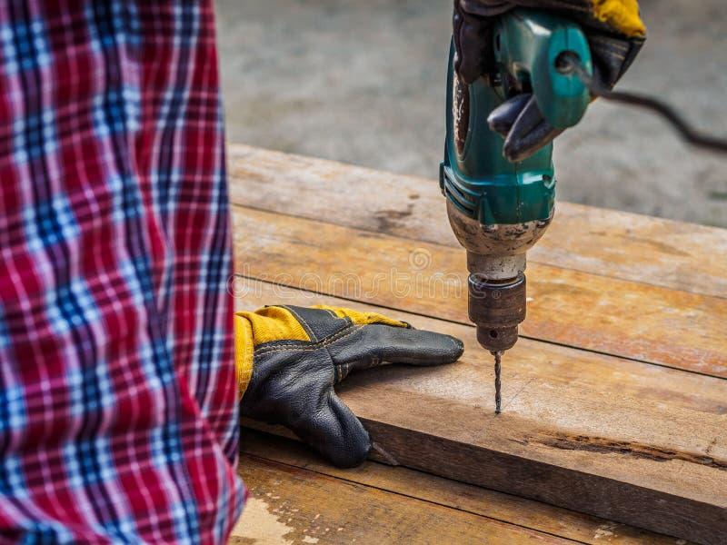 O carpinteiro fura um furo com uma broca elétrica profissão, Ca imagem de stock