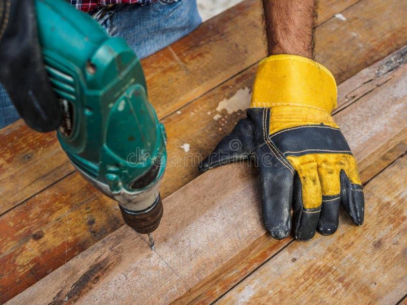 O carpinteiro fura um furo com uma broca elétrica profissão, Ca imagens de stock royalty free