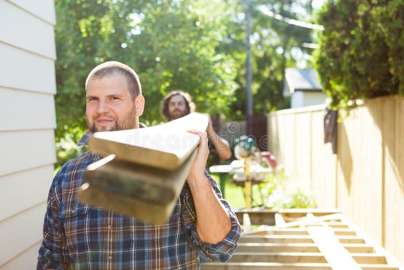 O carpinteiro masculino And Coworker Carrying serra madeira em fotografia de stock