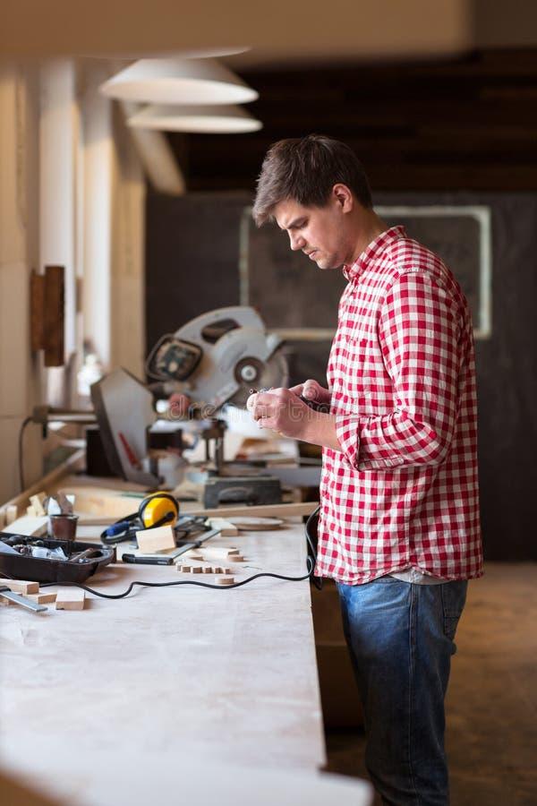 O carpinteiro mestre mói a parte de madeira das ferramentas giratórias de di do brinquedo da madeira imagens de stock royalty free