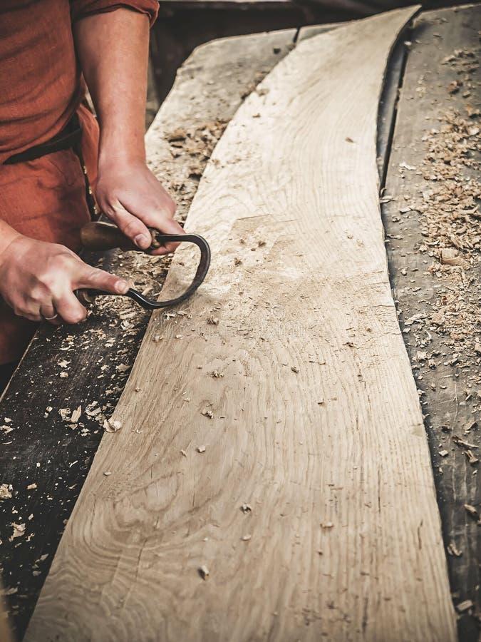 O carpinteiro na roupa medieval do algodão que trabalha com um Drawknife ou uma faca de tiragem ou uma barbeação da tração ou que fotos de stock