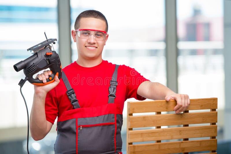 O carpinteiro novo da mobília no conceito industrial foto de stock royalty free
