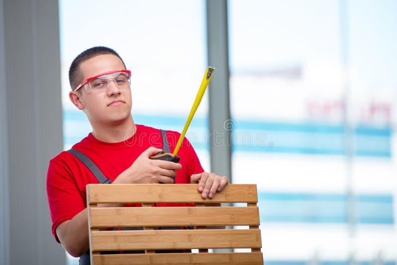 O carpinteiro novo da mobília no conceito industrial fotografia de stock royalty free