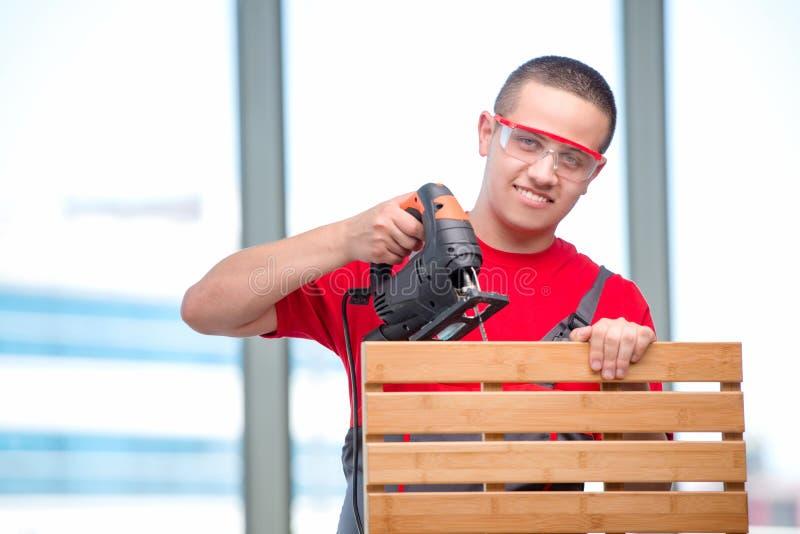 O carpinteiro novo da mobília no conceito industrial fotografia de stock