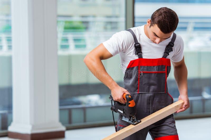 O carpinteiro novo que trabalha no canteiro de obras imagens de stock