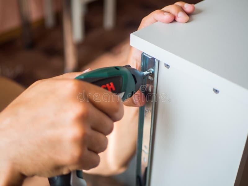 O carpinteiro parafusa os trilhos da mobília à caixa da mobília usando a chave de fenda elétrica, tiro do close up DIY foto de stock royalty free