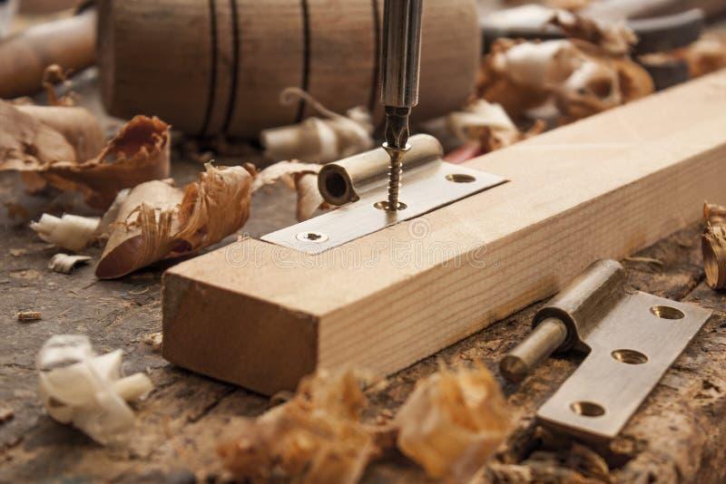 O carpinteiro parafusou uma dobradiça imagens de stock