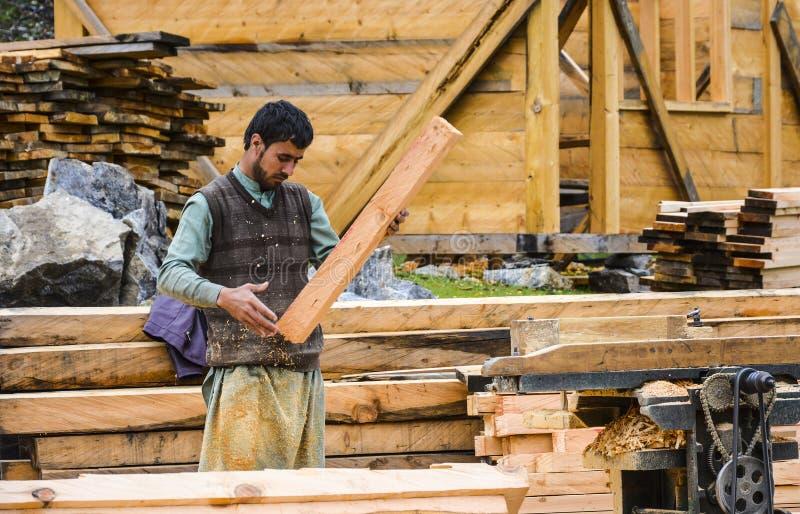 O carpinteiro que corta a madeira com costeleta profissional viu imagens de stock
