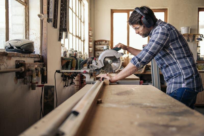 O carpinteiro que corta a madeira com uma mitra viu em sua oficina fotos de stock royalty free