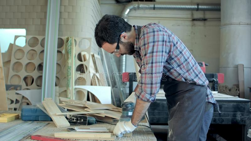 O carpinteiro que trabalha com plaina elétrica e faz anotações em seu caderno na oficina fotos de stock