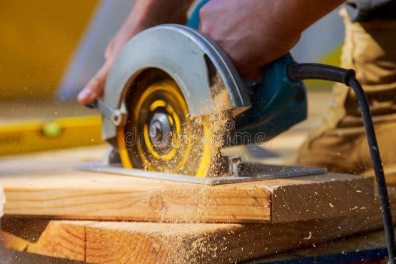 O carpinteiro que usa a circular viu cortando placas de madeira com ferramentas elétricas da mão imagem de stock