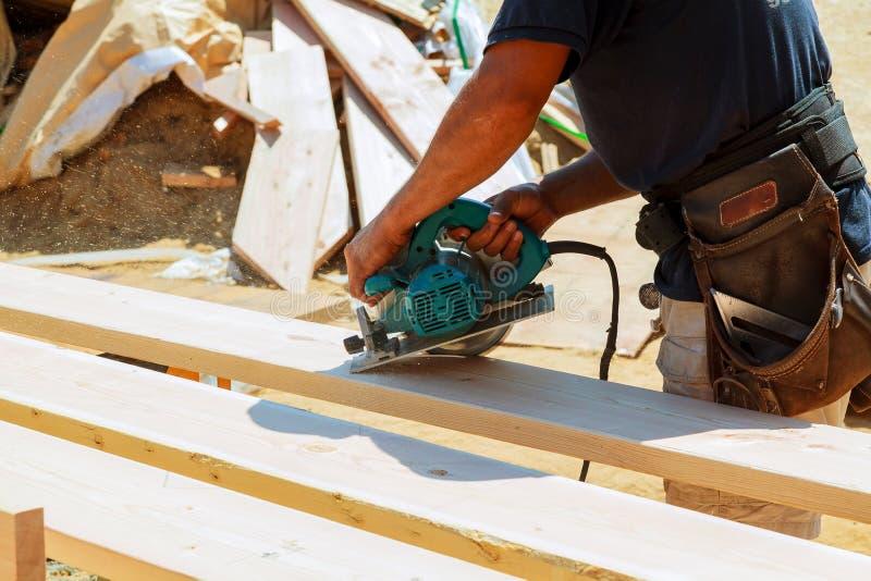 O carpinteiro que usa a circular viu cortando placas de madeira Detalhes da construção do trabalhador masculino imagens de stock