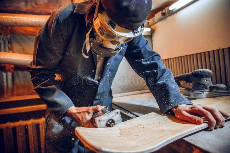 O carpinteiro que usa a circular viu cortando placas de madeira fotografia de stock