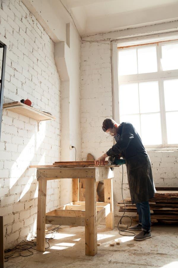 O carpinteiro que usa a mão do poder viu o corte de pranchas de madeira na oficina fotografia de stock