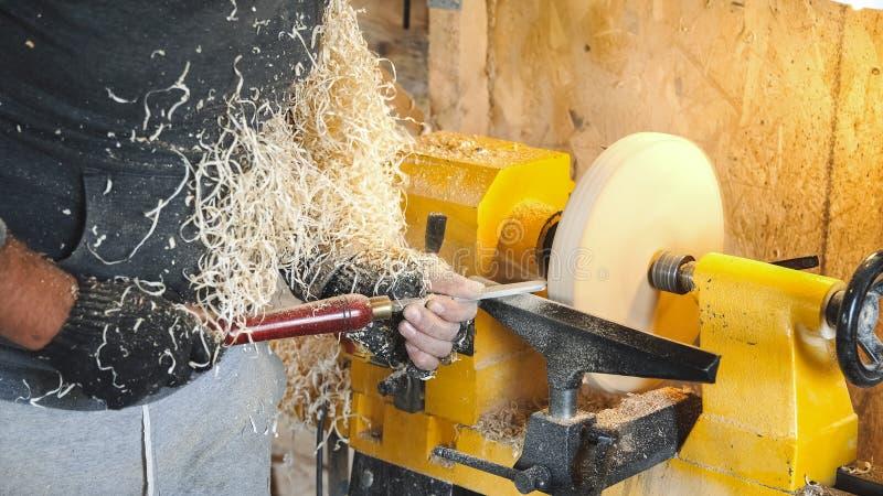 O carpinteiro segura a madeira pelo banco e pelo formão imagens de stock