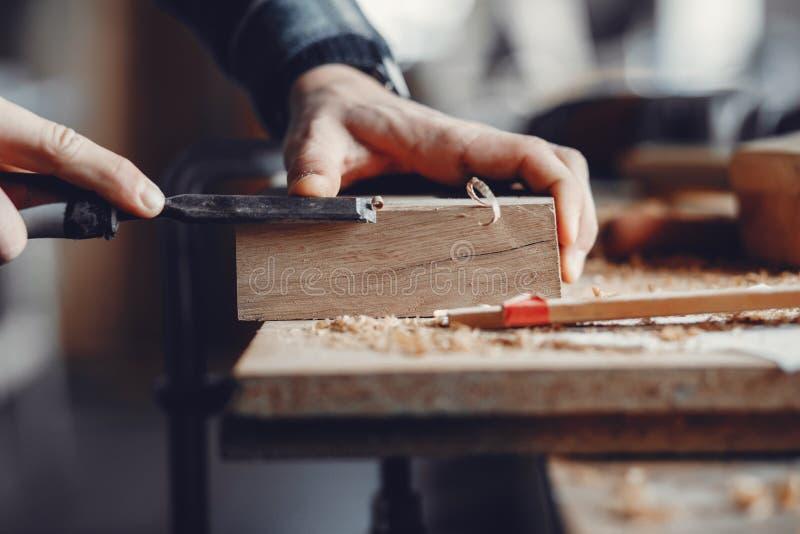 O carpinteiro trabalha com uma árvore fotos de stock