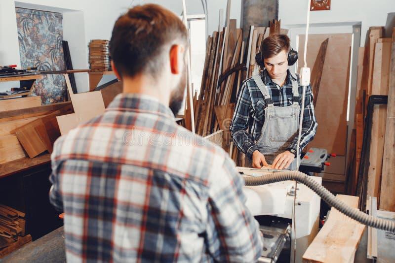 O carpinteiro trabalha com uma ?rvore imagem de stock