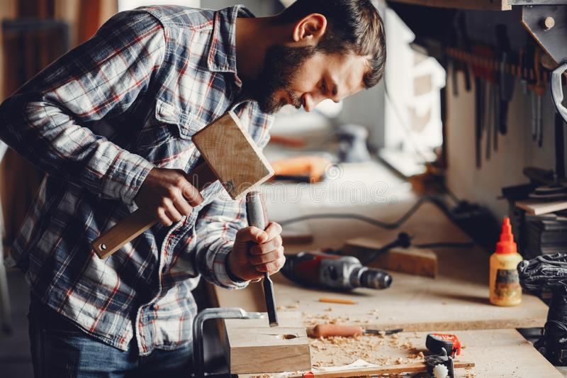O carpinteiro trabalha com uma ?rvore foto de stock
