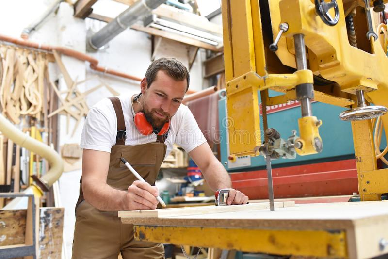 O carpinteiro trabalha em uma obra de carpintaria - oficina para o woodworking e o sawi imagem de stock