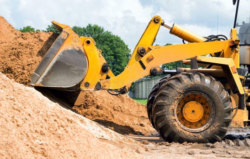O carregador amarelo do trator está pegarando uma cubeta da terra, mecânica, concha com terra foto de stock