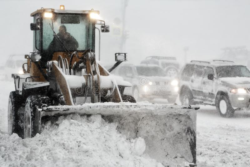 O carregador da roda da parte frontal remove a neve da estrada durante a tempestade do inverno das nevadas fortes, visibilidade p fotos de stock royalty free