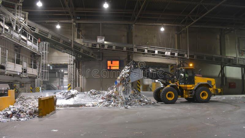 O carregador da roda transporta a papelada para reciclar em um moinho - pa imagem de stock