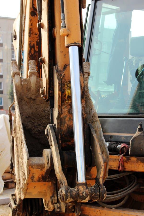 O carregador de sistema hidráulico do pistão do trabalho sujo, cromo chapeou o eixo do cilindro da máquina amarela, detalhe da in fotografia de stock