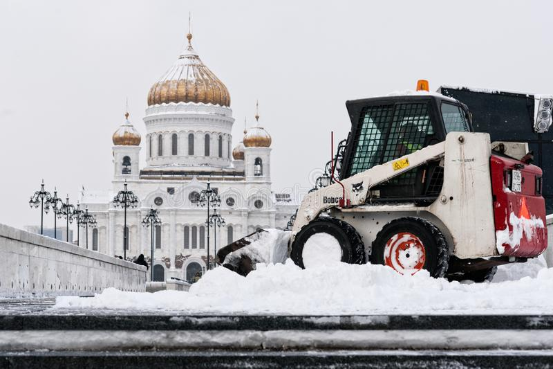 O carregador do lince remove a neve da ponte do patriarca fotos de stock