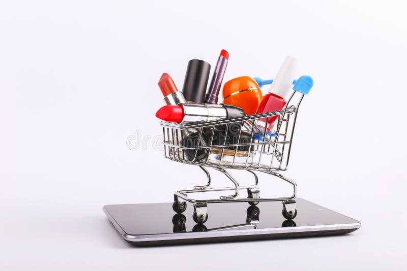 O carrinho de compras com cosm?ticos est? no smartphone Conceito em linha das vendas fotografia de stock
