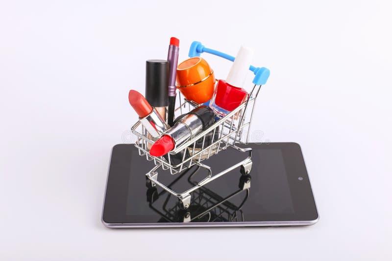 O carrinho de compras com cosm?ticos est? no smartphone Conceito em linha das vendas imagens de stock
