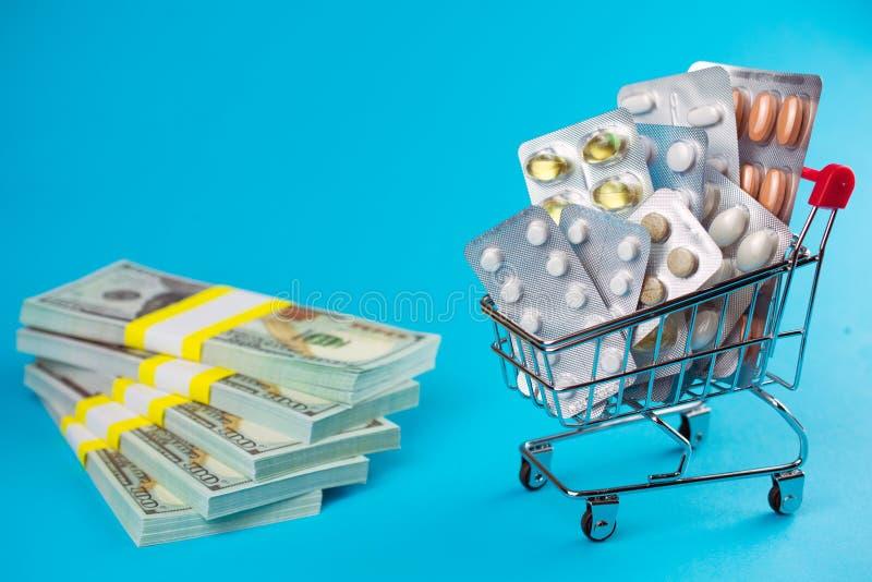O carrinho de compras encheu os comprimidos medicinais vermelhos das tabuletas das c?psulas, punhado do dinheiro do d?lar fotografia de stock royalty free