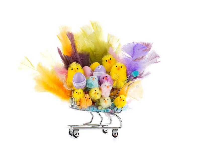 O carrinho de compras encheu-se com as galinhas e as penas felizes coloridas de easter foto de stock