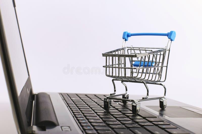 O carrinho de compras est? no port?til Conceito em linha das vendas fotografia de stock