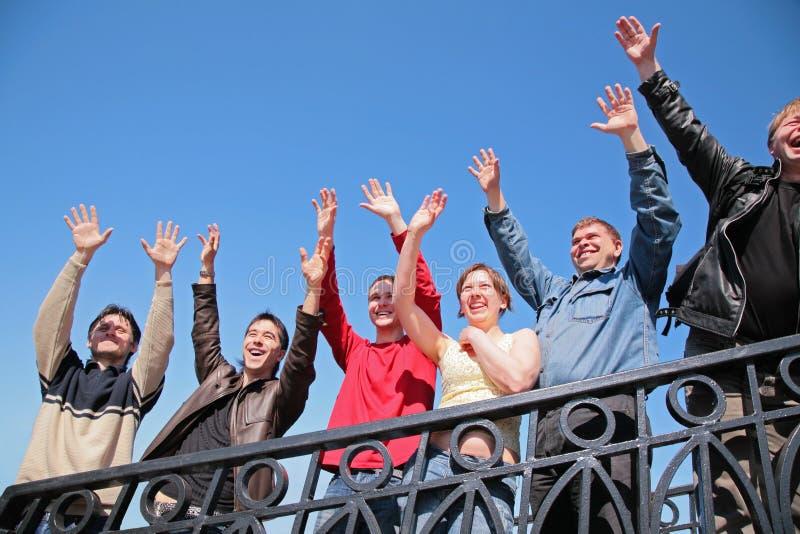 O carrinho do grupo de pessoas com as mãos levantadas dentro cumprimenta fotos de stock