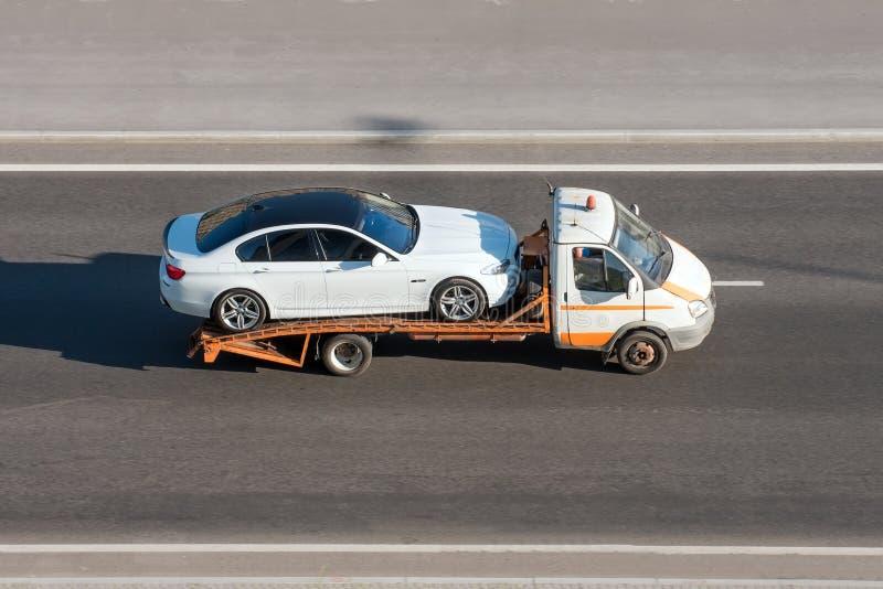 O carro é transportado em um caminhão de reboque da evacuação na estrada foto de stock royalty free