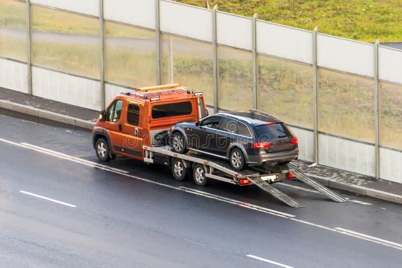 O carro é transportado em um caminhão de reboque da evacuação na estrada imagens de stock