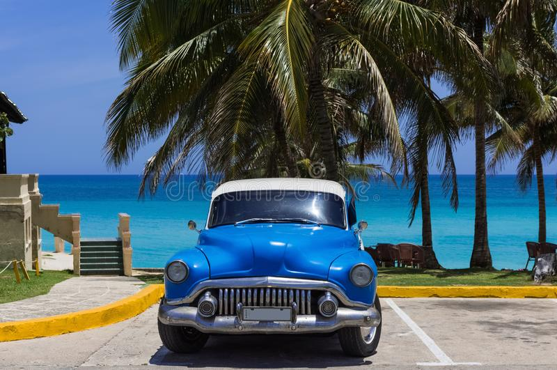 O carro azul americano do clássico de Buick oito estacionou sob as palmas na praia em Varadero Cuba - reportagem de Serie Cuba foto de stock royalty free