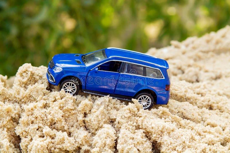 O carro azul do brinquedo aumenta acima fotografia de stock