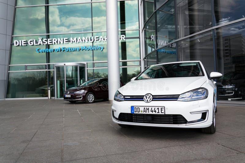 O carro bonde do e-golfe híbrido de encaixe de Volkswagen está pela estação de carregamento na frente do Glaserne Manufaktur - fá imagens de stock royalty free