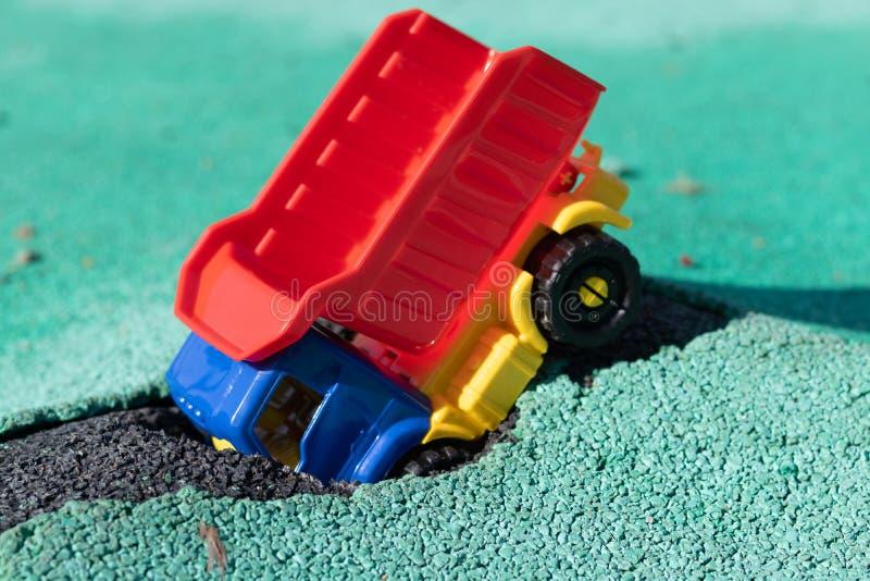 O carro caiu no poço O caminhão plástico do brinquedo com um corpo vermelho teve um acidente Furo em Asphalt Coating A estrada fotos de stock royalty free