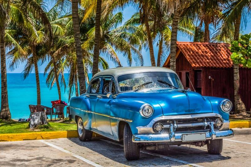 O carro clássico azul americano de Chevrolet com telhado de prata estacionou na praia em Varadero Cuba - reportagem de Serie Cuba fotografia de stock royalty free