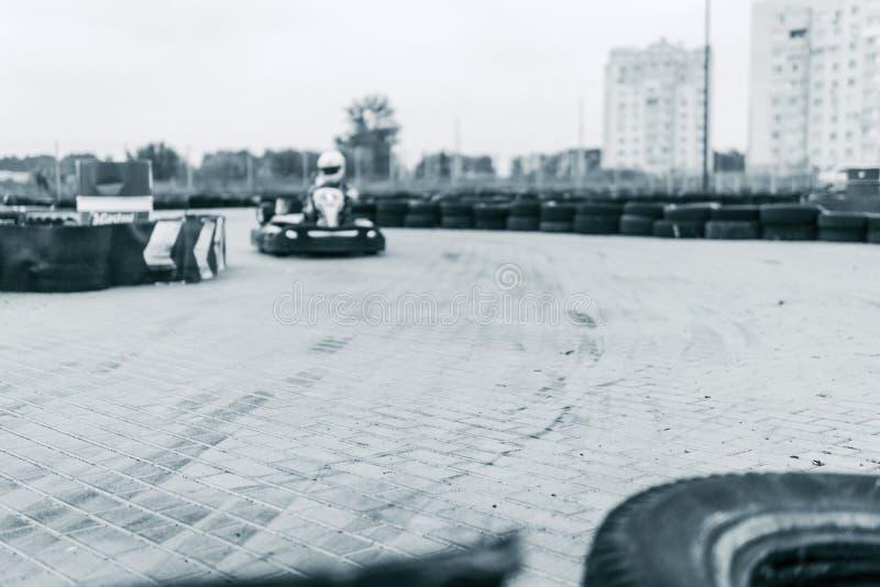 O carro de competência na trilha, campeonato do kart, esportes ativos, divertimento extremo, o motorista mantém suas mãos na roda fotografia de stock royalty free