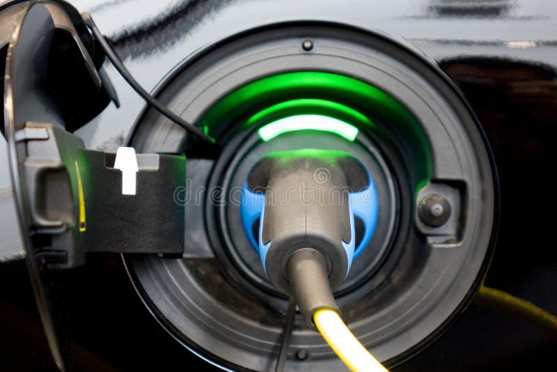 O carro de EV ou o carro elétrico na estação de carregamento com a fonte do cabo distribuidor de corrente obstruíram fotos de stock