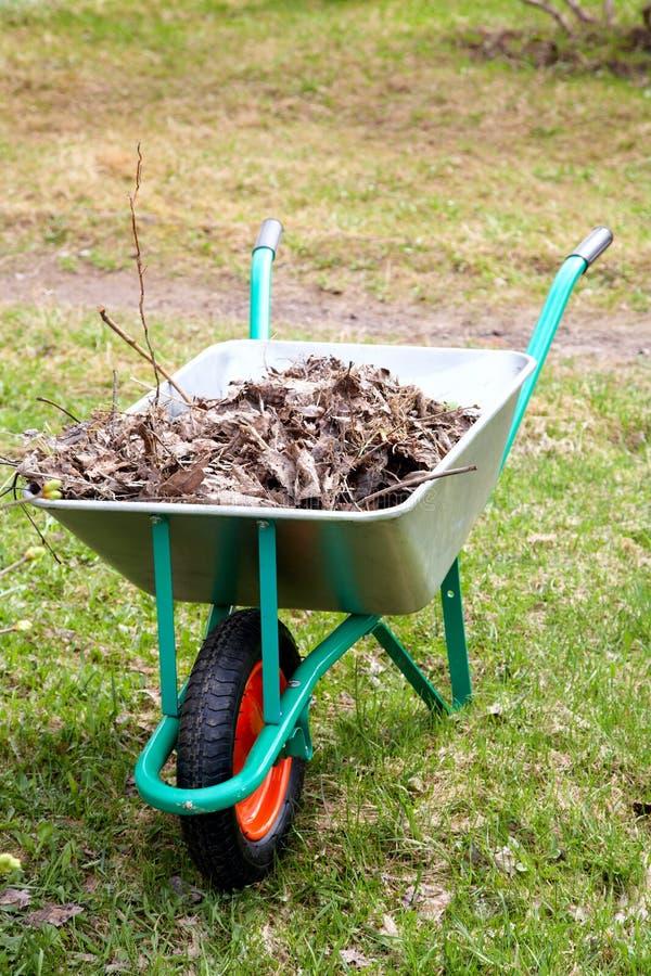 O carro de jardim com o montão das folhas secas fotografia de stock royalty free